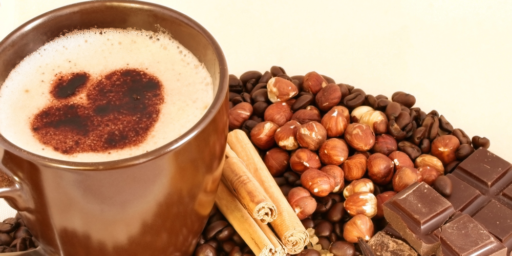 A mug of frothy coffee, surrounded by coffee beans, hazelnuts, cinnamon, vanilla beans, raw sugar, and chocolate chunks.