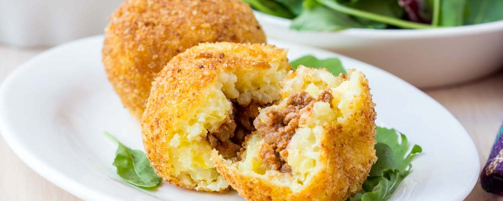 Italian appetizer arancini, rice balls stuffed with meat cooked in deep fat