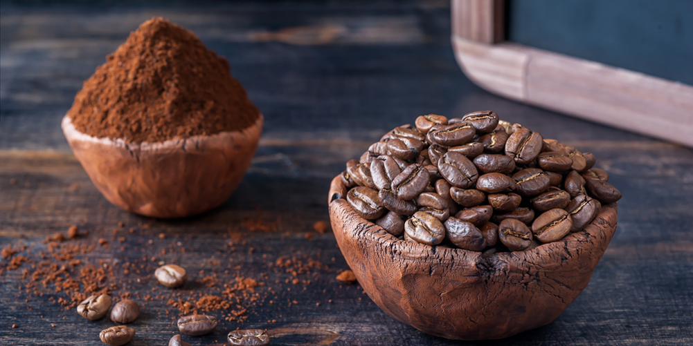 Bowl of coffee beans and ground coffee and menu board on a vintage background