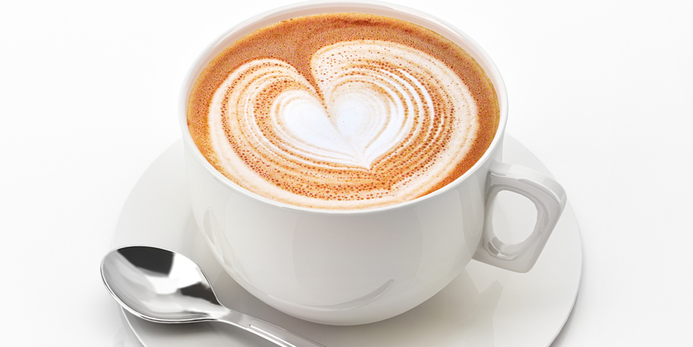 Cappuccino mug close up, with a heart decorated on top of foam. On white background with clipping path.