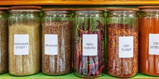 Different spices in jars placed in row