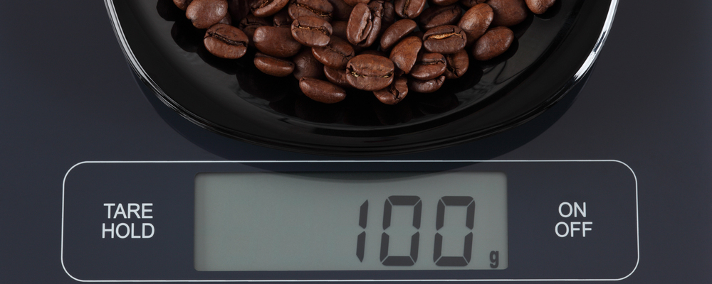 Coffee beans in a black plate on digital scale displaying 100 gram.