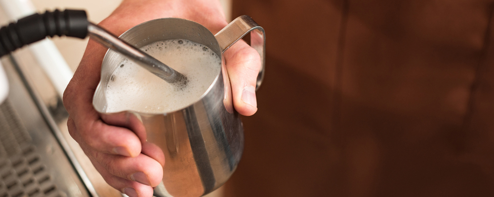 Cropped view of barista filling up steel milk jug