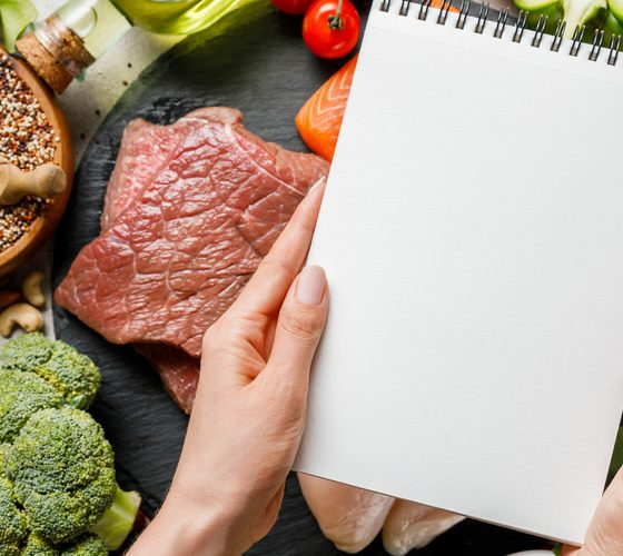 Cropped view of woman holding empty notebook above food