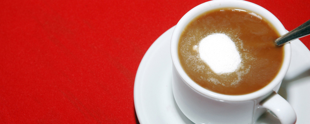 cup of coffee with creamer on the red table