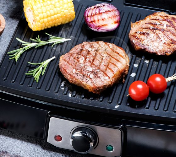 Beef steak with vegetables. Preparation on electric grill