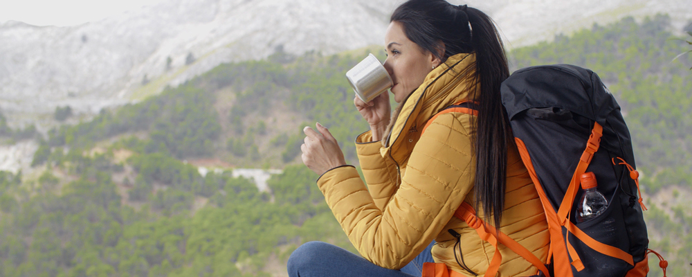 Active attractive young female backpacker taking a break from hiking in the mountains to enjoy a mug of coffee