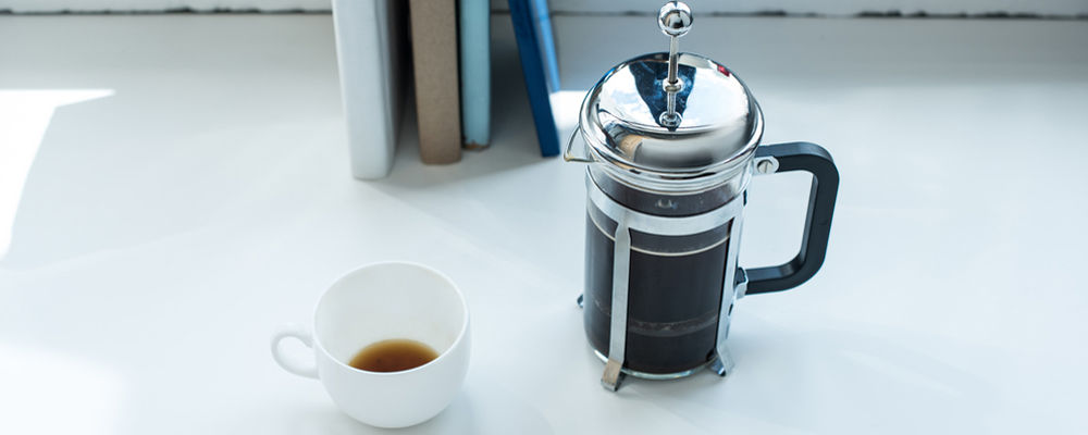 French press with coffee cup