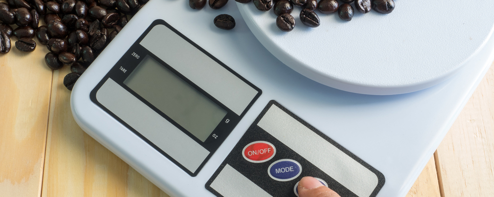 Hand press on digital measuring device and coffee beans