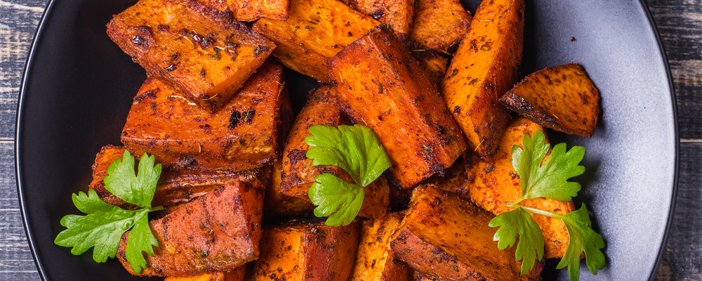 Homemade Cooked Sweet Potato with spices and herbs on dark background.
