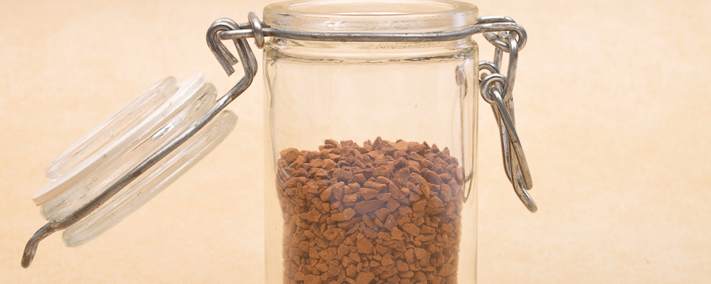 Instant Coffee in open jar on brown background