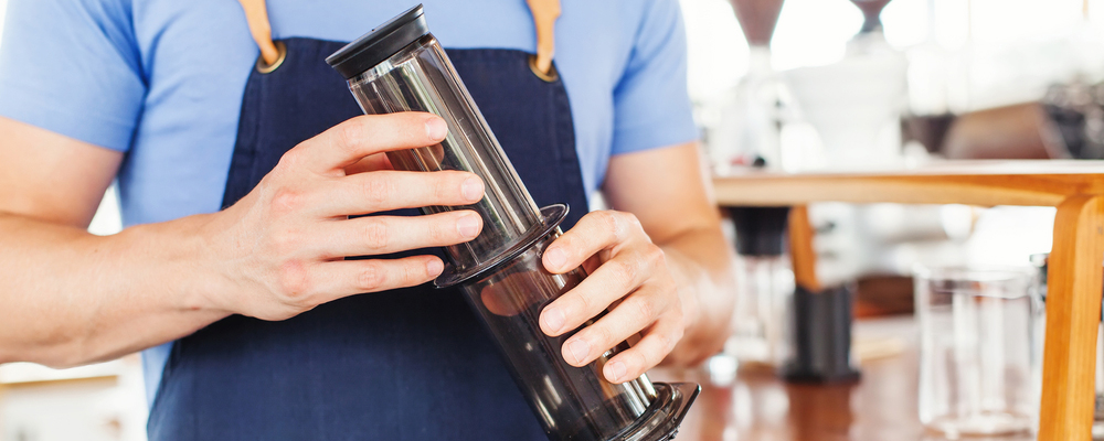 Nontraditional coffee brewing. Hands holding aeropress