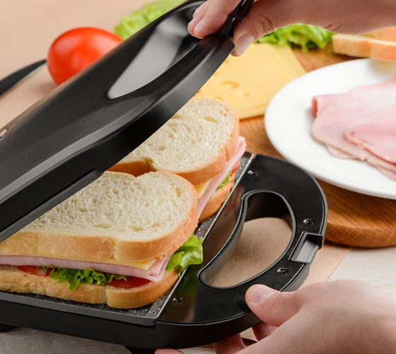 Man using a panini press, close up shot. Easy making of grilled sandwiches for a breakfast.