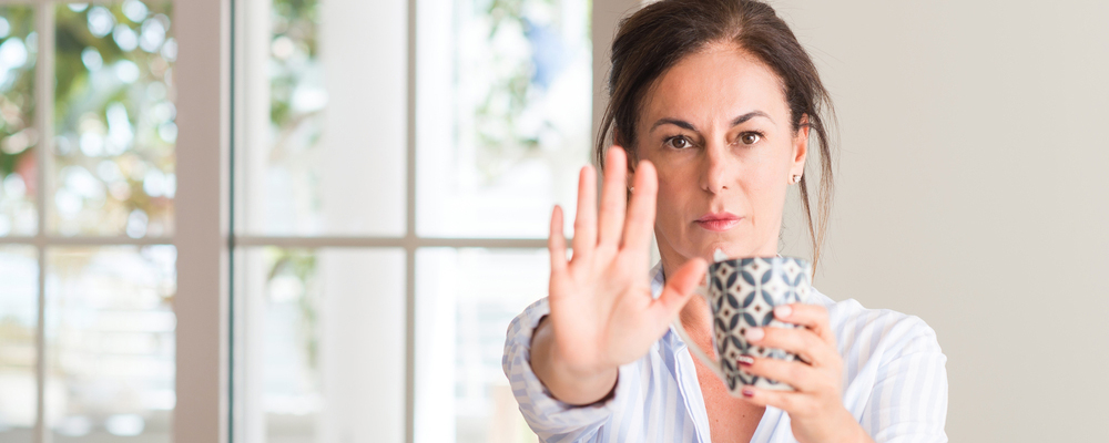 Middle aged woman drinking a cup of tea or coffee with open hand doing stop sign with serious and confident expression, defense gesture