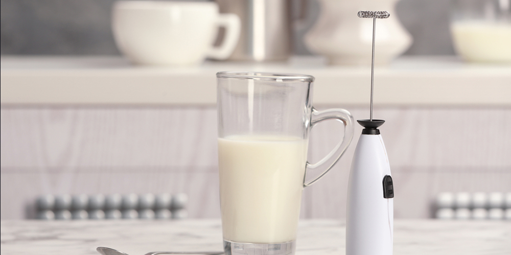 Milk frother device, glass cup and spoon on table in kitchen