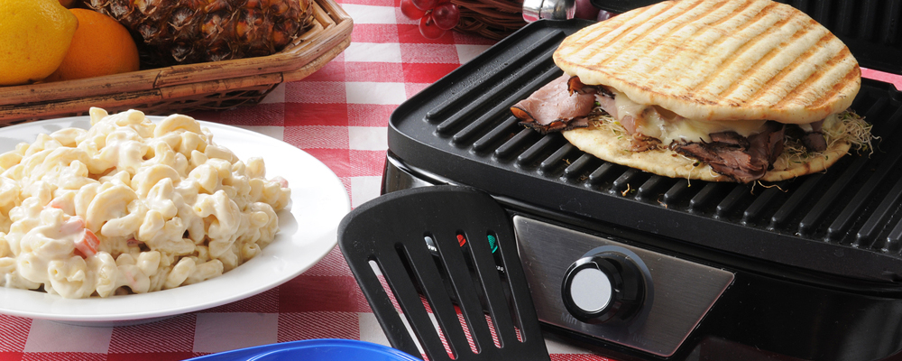 A roast beef and swiss cheese panini being grilled on a picnic table