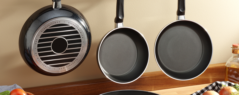 set of black frying pans hanged at kitchen