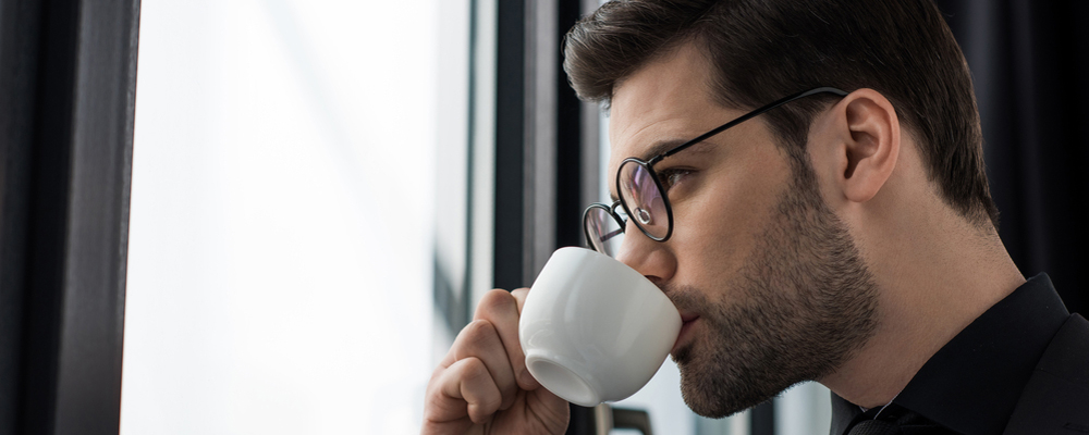 Side view of businessman in glasses drinking coffee