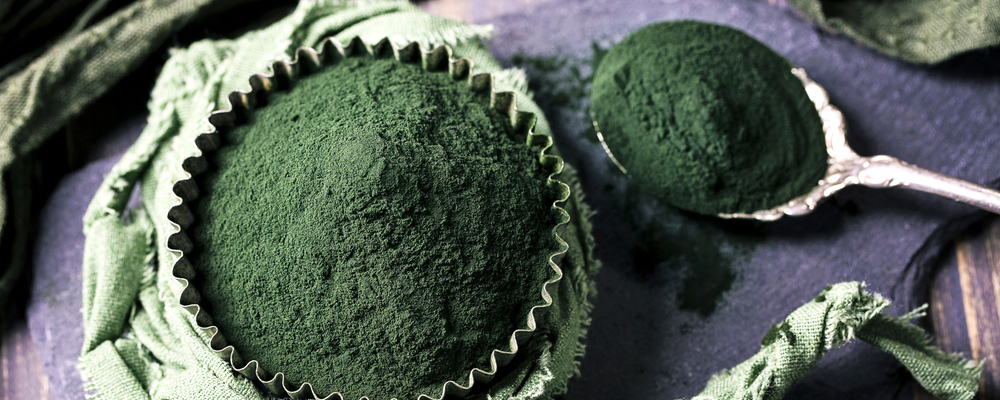 Spirulina powder on a wooden background