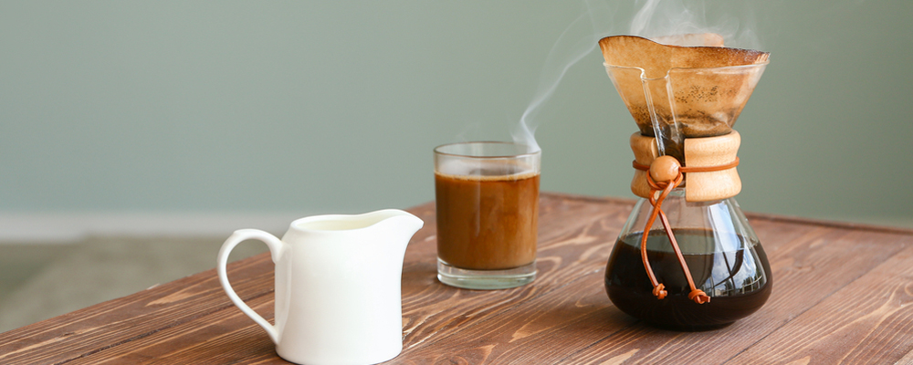 Tasty coffee in chemex and cup with jug of milk on wooden table