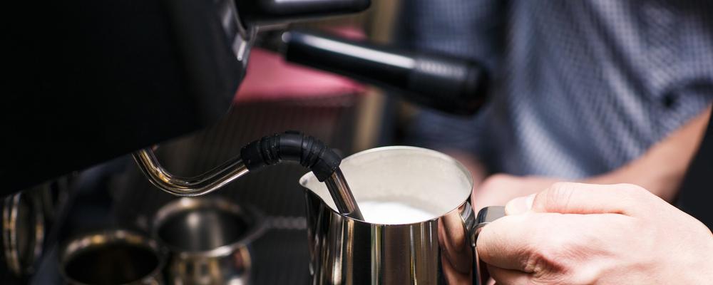 Waiter pouring milk