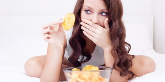 Woman eating potato chips in bed