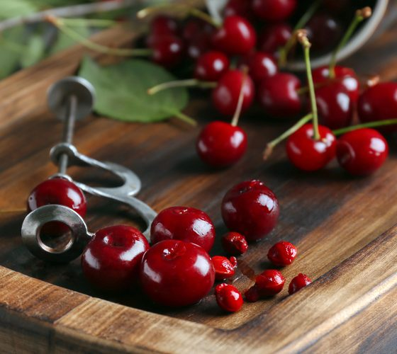 Wooden board with ripe cherries on grey table