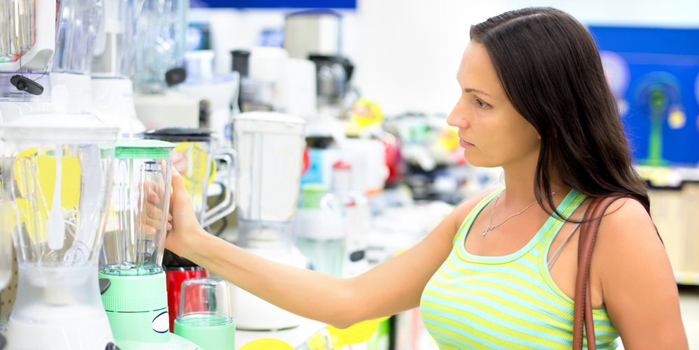 Young woman choosing kitchen mixer blender in Home Appliance Store