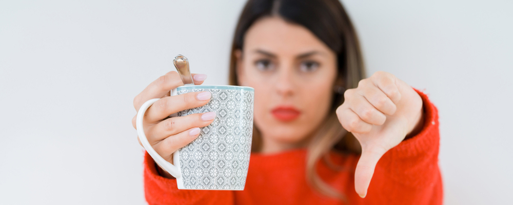 Young woman drinking cup of coffee over isolated background with angry face, negative sign showing dislike with thumbs down, rejection concept