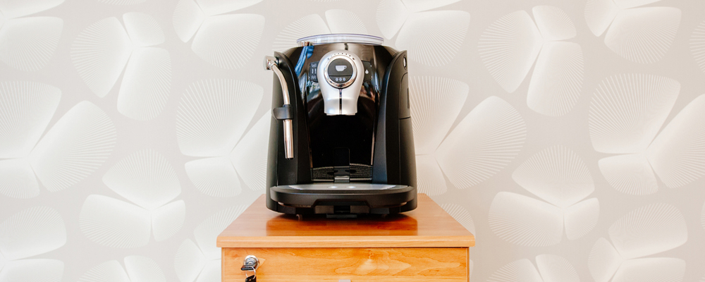 Espresso, cappuccino and americano coffee maker machine which has a coffee grinder on top in a clean modern  office background