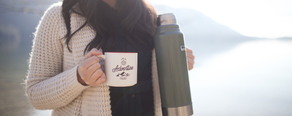 A woman drinking a hot beverage from a thermos