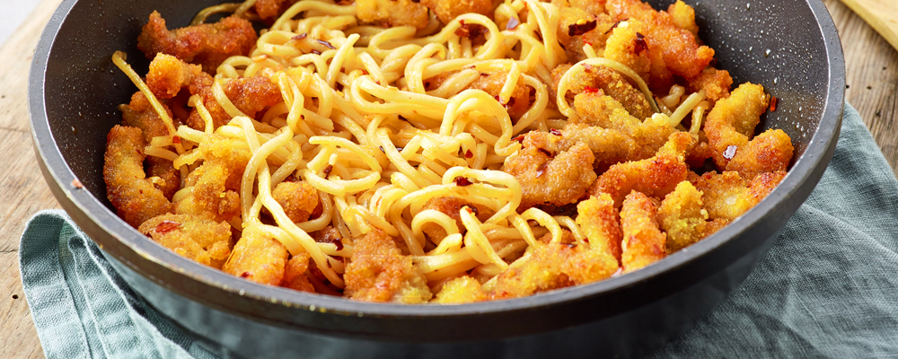 Pan of asian egg noodles with fried meat on wooden table