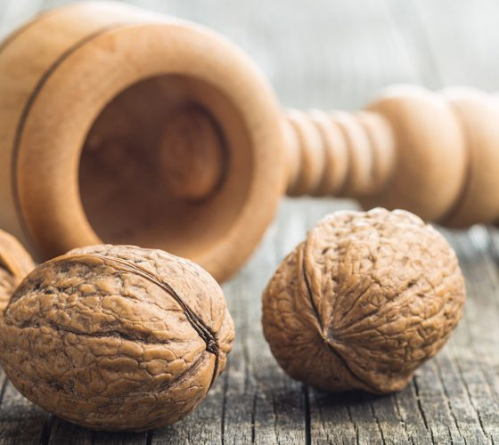 Dried walnuts and nutcracker on wooden table.