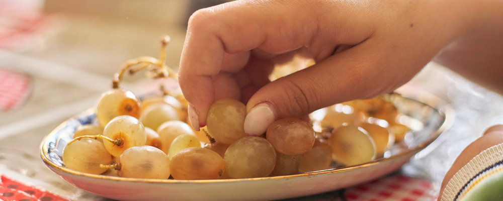 Female hand eating grapes
