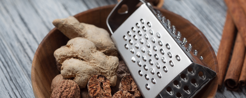 Ginger with nutmeg and grater in bowl on wooden background and various spices