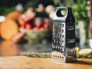 Grater on a wooden cutting board in a restaurant kitchen, fresh vegetables in the background.