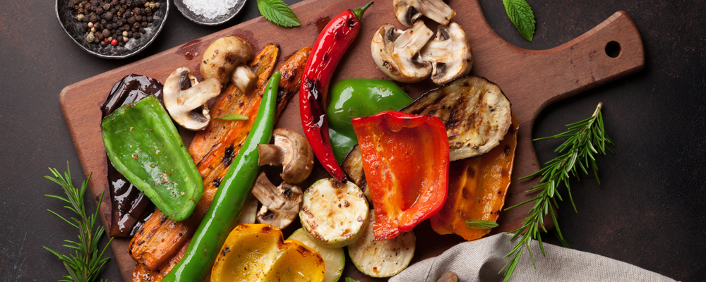 Grilled vegetables on cutting board on dark stone table. Top view