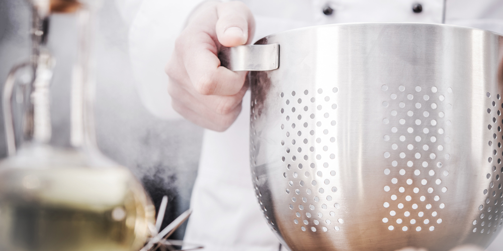 Caucasian Kitchen Chef with Stainless Steel Colander During Dinner Preparation. Closeup Photo.