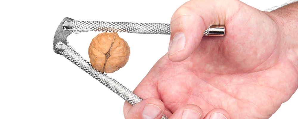 A man squeezes a walnut with a nut cracker.