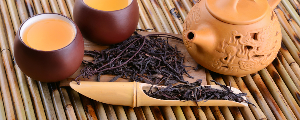 Two cups of aromatic oolong tea on bamboo mat background