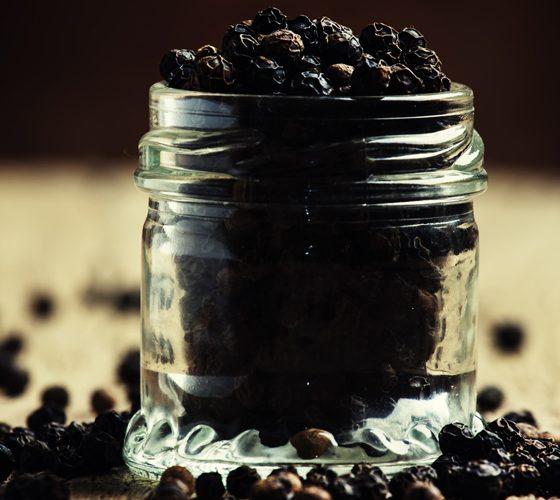 Pea of black pepper in a glass jar