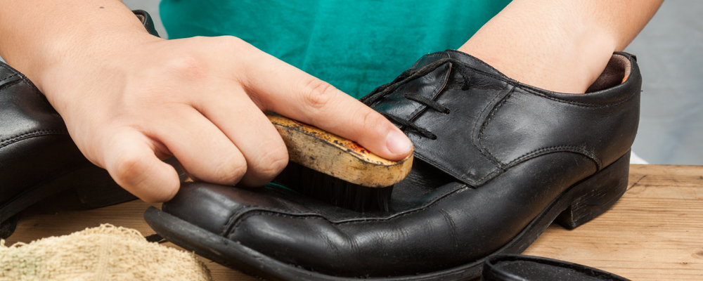 Person polishing and restoring worn out men's formal shoes.