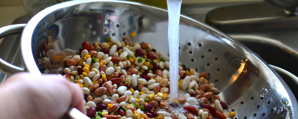 Rinsing a mix of dried beans with colander
