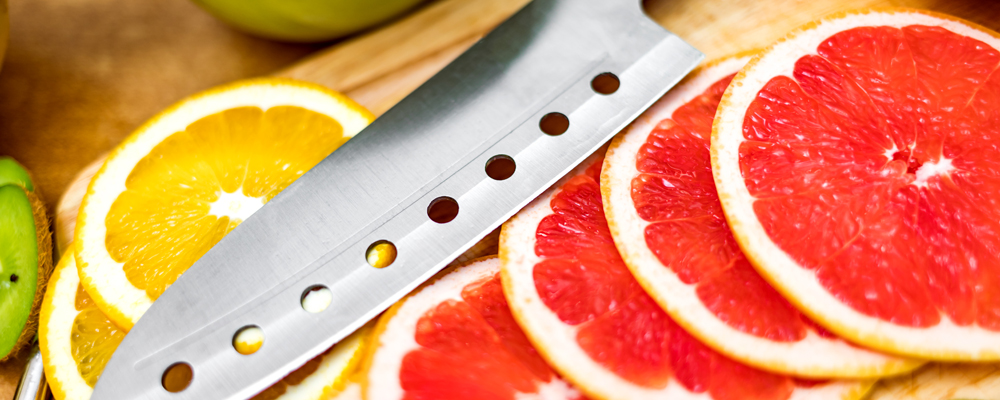 Sharp kitchen knife on cutting Board next to sliced grapefruit and other fruits