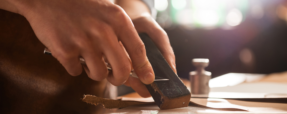Close up of a shoemaker sharpening a knife at his workshop