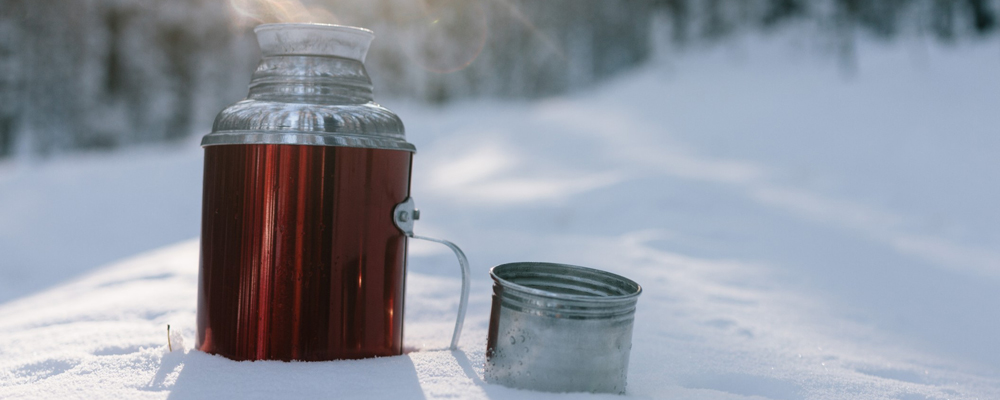 Thermos half buried on a white snow