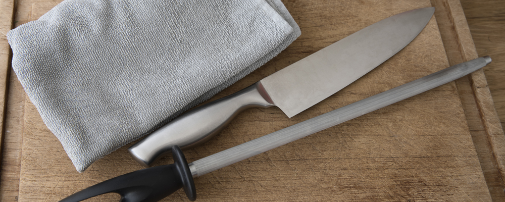 Chef's knife, honing steel and towel on cutting board, preparing for knife honing.