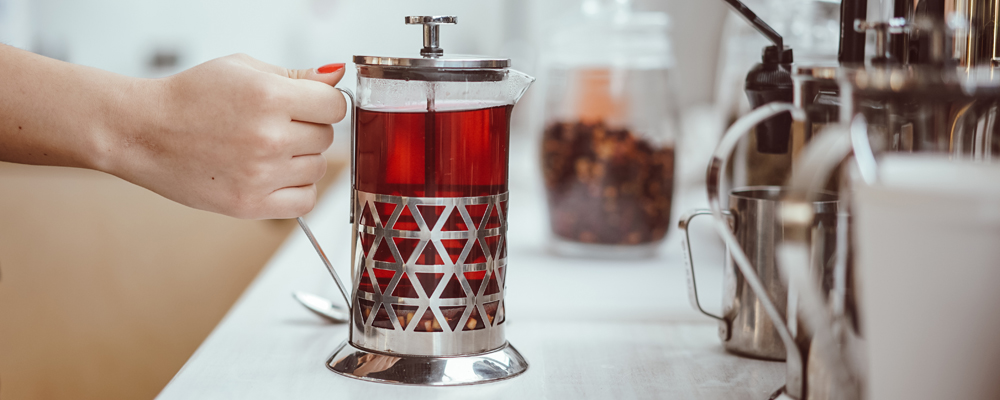 fresh berry tea in French press on the table, close view