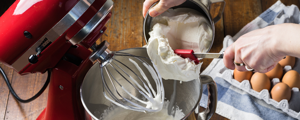 putting cheese cream in bowl of standing red kitchen aid mixer w