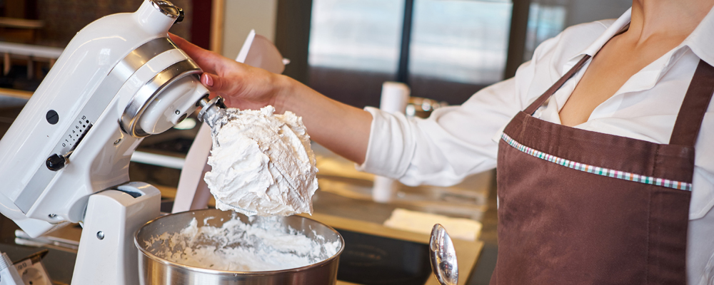 Woman using mixer standing at counter in her apron. Making dessert in pastry